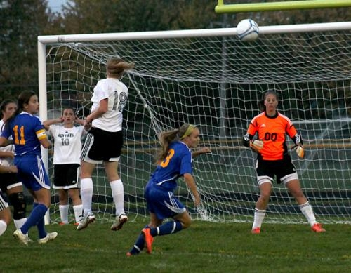 Hannah Williams (left), a member of the Huntington North High School girls' varsity soccer team, heads the ball on a Homestead throw-in while teammate Paige Coolman (right) stands ready to defend the goal.