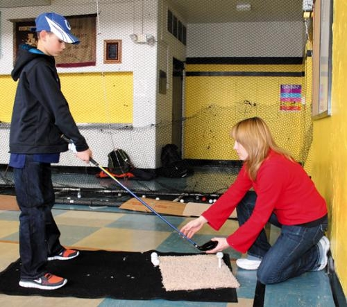 Danielle Albertson (right), coach of the newly-formed Huntington Catholic School golf team, helps sixth-grader Sam Mickley with his tee shot in the team's practice area set up in the school's gym.