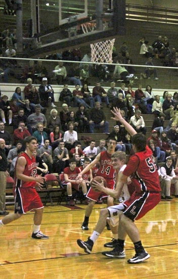 Defenders from visiting Logansport converge on Huntington North's Kyle Platt (middle) as he enters the paint in a game on Friday, Feb. 15. The Vikings lost 68-67.