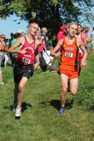 Huntington North's Matt Dewitt (left) runs alongside Daniel Messsenger of Warsaw during the boys' varsity race at the Huntington North Cross Country Invitational on Saturday, Aug. 24, at the Huntnigton University cross country course.