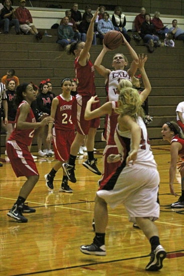 Huntington North's Allyson Trout (middle) puts up a jumper in traffic while a defender from visiting Richmond goes for the block during the girls' varsity basketball team's game on Saturday, Dec. 15. The Lady Vikings got their first win of the season.