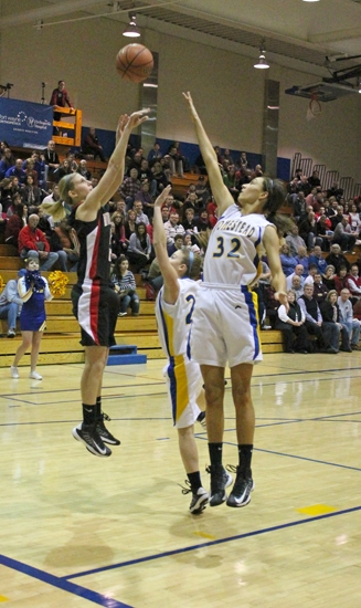 Huntington North's Allyson Trout gets her shot off above the outstretched arm of Homestead Lindley Kistler in action at the Homestead Girls' Basektball Sectional on Friday, Feb. 8. The Lady Vikings fell, 43-35.
