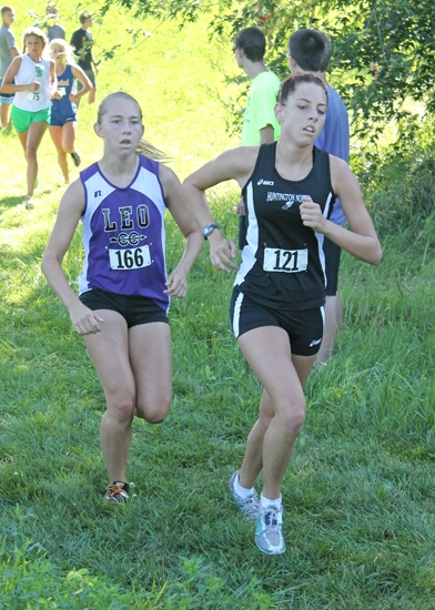 Huntington North junior Taryn Doering (right) stays ahead of Leo's Breeann Fawcett during the girls' varsity race a the Huntington North Cross Country Invitational on Saturday, Aug. 24, at Huntington University's course.