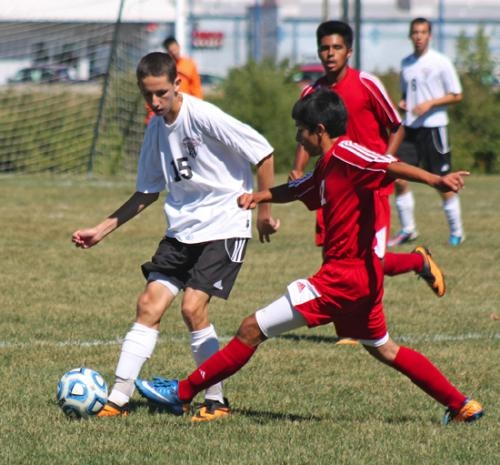 Huntington North's Alex Hosler (left) contends for the ball with a visiting Anderson player during the boys' varsity soccer team game against the Indians on Saturday, Sept. 14. The Vikings won 8-2.