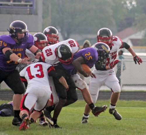 Marion running back Jonathan Decker (front middle) is swarmed by Huntington north tackler Taylor Boxell (left) and Matthew Mounsey in action at Marion on Saturday,Sept. 22. The Vikings won 34-31.
