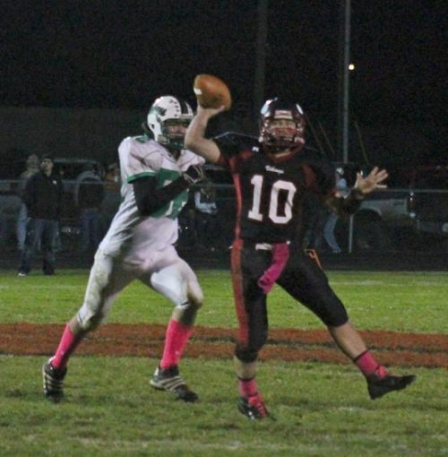 Huntington North quarterback Drew Schnitz (right) concentrates on his target downfield while a defender from visiting New Castle bears down on him in a game on Friday, Oct. 12. Schnitz threw three touchdown passes and the Vikings won 28-14.