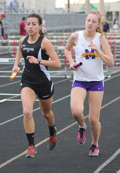 Huntington North's Karson Rowe (left) edges in front of her Marion rival during the second leg of the 3,200-meter relay  at Kriegbaum Field on Tuesday, April 9. The Lady Vikes won the race and the meet.
