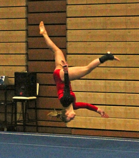 Mikayla Carpenter, a senior on the Huntington North gymnastics team, goes upside down during a maneuver in the floor exercise at the Concordia Lutheran Sectional on Saturday, March 8.