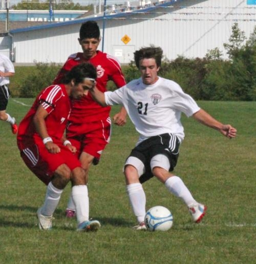 Eric Fruit (right) tries to hold onto the ball for the Huntington North High School boys' varsity soccer team against Alfredo Vasquez of visiting Wayne on Saturday, Sept. 15. The game ended in a 3-3 tie.