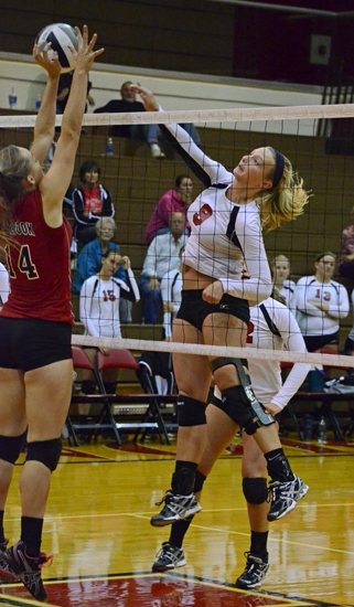 Lady Viking Jessie Drew spikes one against the defense of Eastbrook during the Huntington North High School lvasity volleyball team's sweep on Wednesday, Sept. 19.
