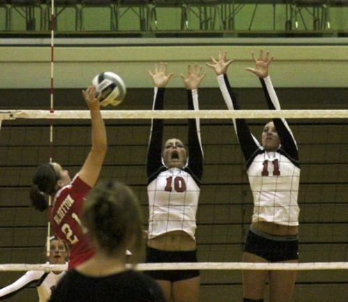 Huntington North defenders (from center) Madi Canady and Josie Beaver put up a wall of hands as Bluffton's Emma Thompson tries to spike the ball in volleyball play at HNHS on Monday night, Aug. 19.