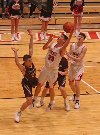 Zach Daugherty uses his left hand as he goes for a shot under the basket against visiting Columbia City on Friday night, Jan. 11. Daugherty scored a team-high 12 points as the Vikings won, 41-29.