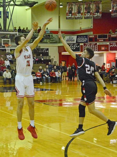 Huntington North's Hank Pulver unleashes a three-pointer over Manchester's Kamdyn Lester in action at North Arena on Saturday, Dec. 9. Pulver had a game-high 18 as the Vikings won big, 59-32.