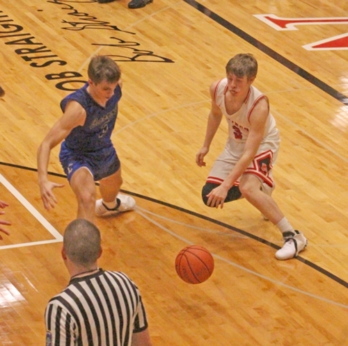 Keegan Bartrom (right), a senior on the Huntington North High School boys' varsity basketball team, attempts to dribble past a Carroll defender during a game on Tuesday, Feb. 12, at North Arena. The Vikings edged the Chargers, 40-38.