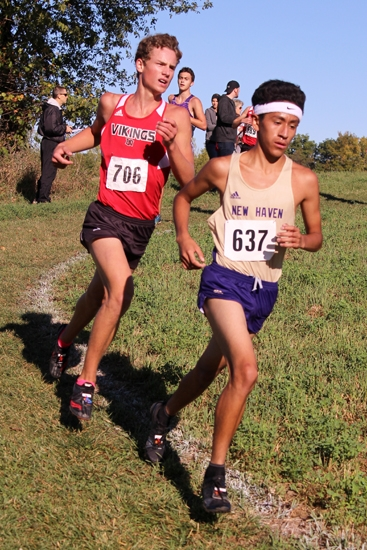 Nolan Young (left), a senior on the Huntington North High School boys' varsity cross country team, keeps pace with New Haven's Luis Saldana on the Huntington University Course during the Northeast 8 Conference championship race on Saturday, Sept. 30. Young placed 15th in 17:14.5 to help the Vikings win the race.