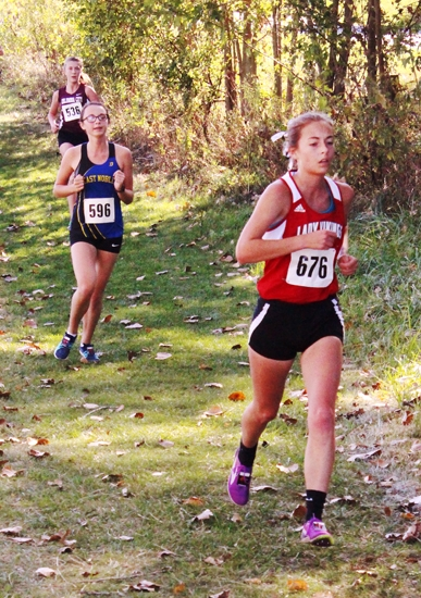 Emma Melcher (right), a senior on the Huntington North High School girls' varsity cross country team, competes in the Northeast 8 Conference championship race on Saturday, Sept. 30, at the Huntington University Course. The Lady Vikings placed second with a score of 60.