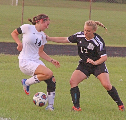 Veronika Russell (right), a junior on the Huntington North High School girls' soccer team, plays defense against Warsaw's Sydney Wiedeman during the championship game of the South Side Sectional on Saturday, Oct. 7. The Lady Vikings lost in overtime, 3-2.