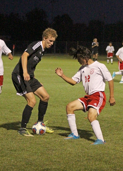Huntington North senior Caleb Smith maneuvers around a Fort Wayne Wayne defender in action Wednesday evening, Oct. 2, at the Warsaw Soccer Sectional. Smith scored the Vikings' lone goal in regulation, and HNHS won the game in a shootout.