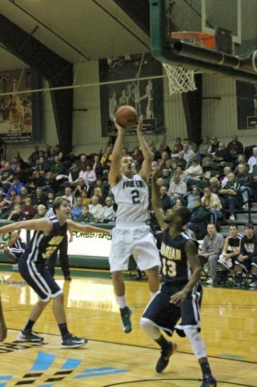 Colin Featherston (middle) elevates in the paint as John Goodlow, of visiting Marian, puts up a hand to stop him in the first half of the Huntington University men's basketball  game against the Knights on Tuesday, Nov. 27.