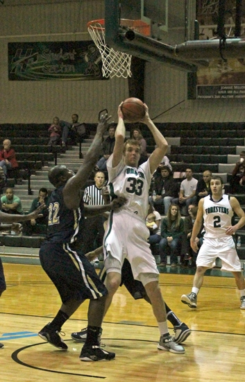 Huntington University center Alec Peterson fights off a pair of University of Akron-wayne defenders down low in the Foresters' 90-50 win on Monday, Dec. 17.