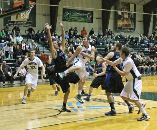 Huntington University guard Colin Featherston (center) tries to pass around the University of Saint Francis defense to teammate Alec Peterson (No. 33, left) during play on Saturday, Jan. 19.