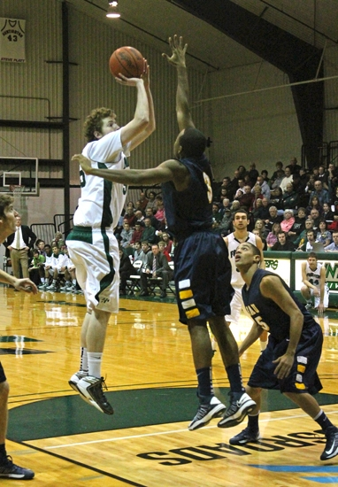 Huntington University forward Shane Merryman launches a jumper over the outstretched arm of Rob Hogans of Spring Arbor University on Saturday, Feb. 16. The Foresters lost, 75-58.
