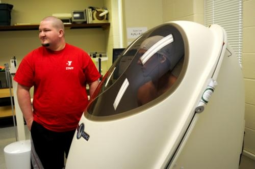 Rodney Forrister (left), a sport and exercise major at Huntington University, assists John Goodman, of the University of Notre Dame, with the Bod Pod, a machine that measures body composition. Goodman is preparing for the NFL's upcoming combine.