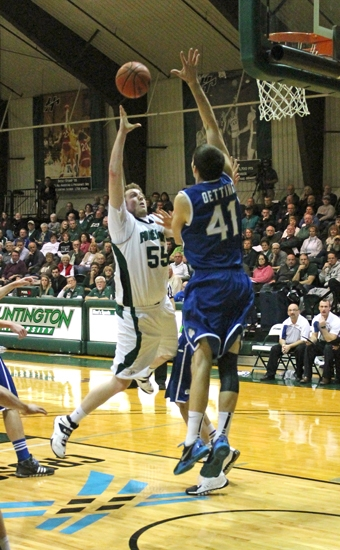 Huntington University forward Shane Merrymanlofts the ball toward the hoop over the outstretched arm of Bethel's Patrick Oetting on Tuesday night, Feb. 11, at Platt Arena.