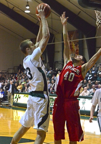 Huntington University center Alec Peterson goes up with a shot over Grace's Kyle Fillman in first round Crossroads League Tournament action at Platt Arena.