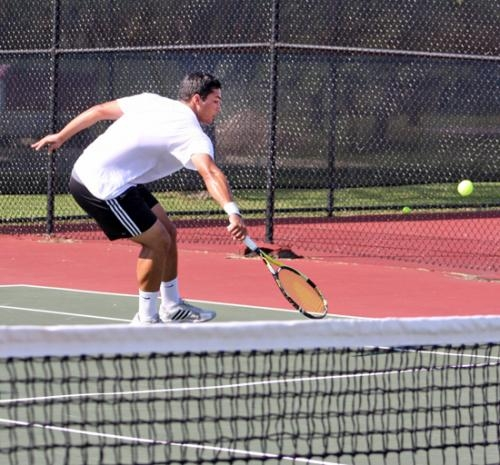 Jose Hungria backhands a shot against Cornerstone University in doubles play with teammate Vlad Khudziy on Friday, Aug. 31 at the HU tennis courts.