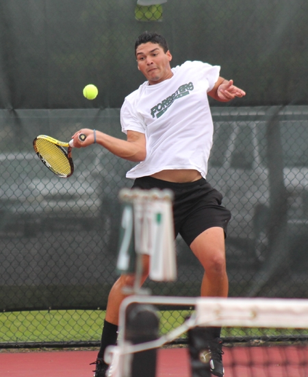 Huntington University tennis player Jose Hungria takes an awkward swing during first doubles play against visiting Grace on Tuesday, Sept. 25. Hungria and his partner, Vlad Khudziy, lost the match, 3-8.