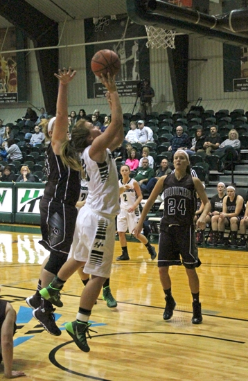 Amelia Recker (middle) puts up a shot under the hoop for the Huntington University women's basketball team in the first half of its season-opening game against visiting Aquinas College on Saturday, Nov. 2.