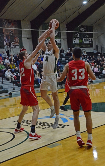 Huntington University center Klajd Kiri goes up for a short jumper over Seth Maxwell of Indiana Wesleyan University in action at Platt Arena on Tuesday night, Feb. 11. The Foresters lost to the No. 3 Wildcats, 97-64.