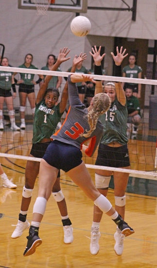 Huntington University freshmen Tya Bynum (left) and Anna Lewis put up a block wall against Savannah Nott of Baker University on Friday night action at the Forester Invitational at Huntington University. HU won three of four games over the weekend.