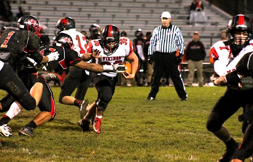 Huntington North senior running back Austin Rosen (fourth from left) takes a handoff from senior quarterback Keenan Leichty (third from left) and bolts toward an opening in the North Side defense during the Vikings' sectional contest on Friday, Nov. 1.