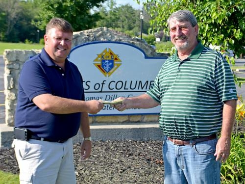 Doug Boone (right), coordinator of the Denny Klepper Memorial Golf Outing, hands a check from the proceeds of the event to Tim Kaufman, Knights of Columbus No. 1014 Grand Knight. The event was held on June 14.