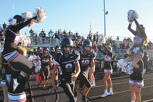 Huntington North High School cheerleaders line the entry onto Kreigbaum Field as HNHS football players leave the locker room to take the field before the start of a game this past season. Five HNHS football team members were named NE8 Football All-Conference team members for 2020.