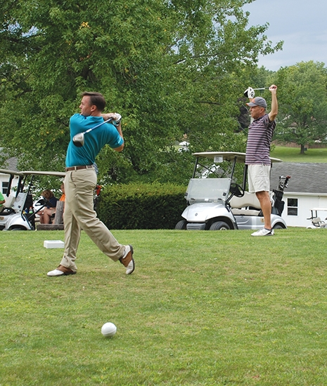 Steve Petry (left) tees off on the first hole at Norwood Golf Course during the Parkview Huntington Golf Classic on Aug. 24. One of Petry's teammates, Mark Parker, watches his drive.