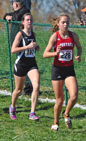 Kayla Patrick (left), a senior on the Huntington North High School girls' cross country team, runs with Portage's Kyra Ball in the IHSAA Girls' Cross Country State Finals in Terre Haute on Saturday, Oct. 27.