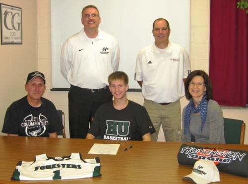 Columbia City High School basketball player Daniel Woll (front center) signs a letter of intent to play basketball at Huntington University recently.
