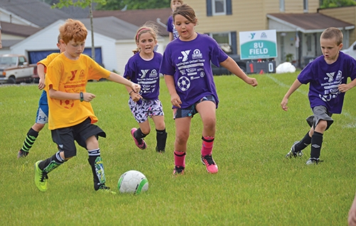 Lightning team member Joshua Lippe (in the yellow shirt at left) battles players from the Storm team (in purple shirts from left) Lillian Blair, Gracie Briggs and Noah Alwine in the Parkview Huntington Family YMCA fall soccer league. Registration for the upcoming season is open now until Aug. 11.